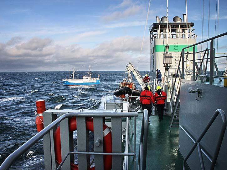 BLE- Inspektoren bereiten ein Speedboot vor. Im Hintergrund wartet der Fischkutter auf die Kontrolle.