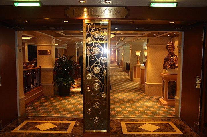 Eine Büste von Königin Elizabeth II. grüßt die Passagiere am Eingang des Queens Room an Bord der QUEEN ELIZABETH.